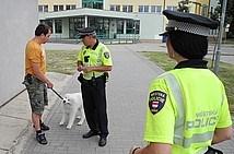 straznik hovori s panem, ktery venci psa