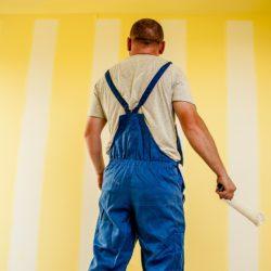 muz maluje stěnu
