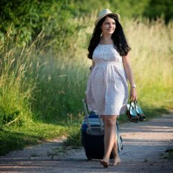 mladá žena s cestovním kufrem